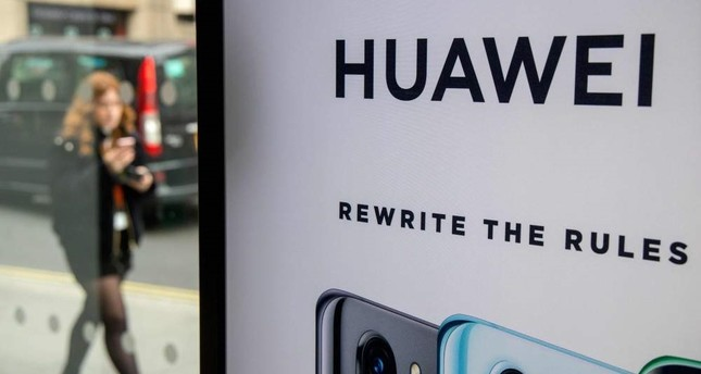 In this file photo taken on April 29, 2019, a pedestrian walks past a Huawei product stand at an EE telecommunications shop in central London. AFP Photo
