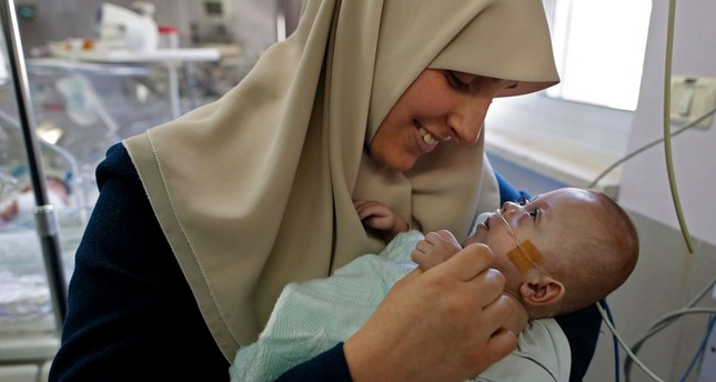 Gazan Jumana Daoud carries her 7-month-old daughter Maryam at Makassed Hospital in Israeli-annexed east Jerusalem on February 20, 2017. (AFP Photo)