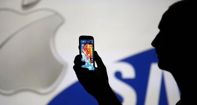 A man is silhouetted against a video screen wıth Apple and Samsung logos as he poses with a Samsung S4 smartphone in Zenica, on August 14, 2013. (REUTERS Photo)