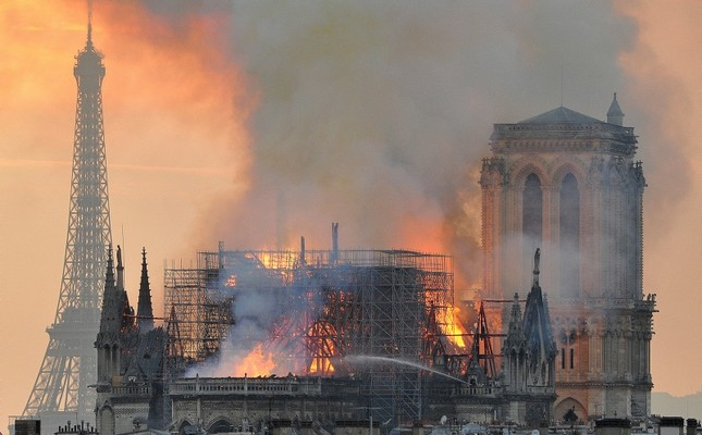 In this image made available on Tuesday April 16, 2019 flames and smoke rise from the blaze after the spire toppled over on Notre Dame cathedral in Paris, Monday, April 15, 2019. (AP Photo)