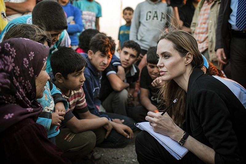 This June 18, 2013 photo shows special envoy Angelina Jolie taking notes as she speaks with Syrian refugees in a Jordanian military camp based near the Syria-Jordan border. (AP Photo)