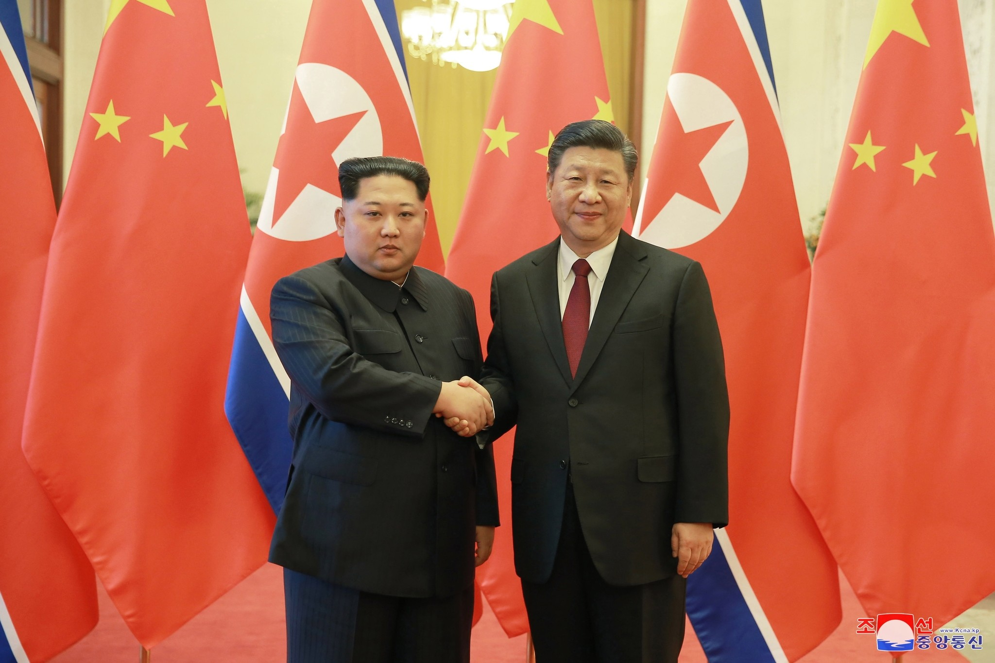 An undated photo released on 28 March 2018 by the official North Korean Central News Agency (KCNA), shows North Korean leader Kim Jong-un (L) shaking hands with Chinese President Xi Jinping (R) during a visit to Beijing, China.