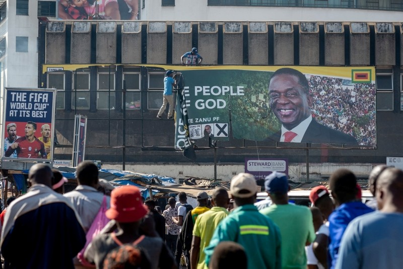 People remove a billboard of ZANU-PF's Emmerson Mnangagwa during a protest against polling results in Harare, Zimbabwe, 01 August 2018. (EPA Photo)