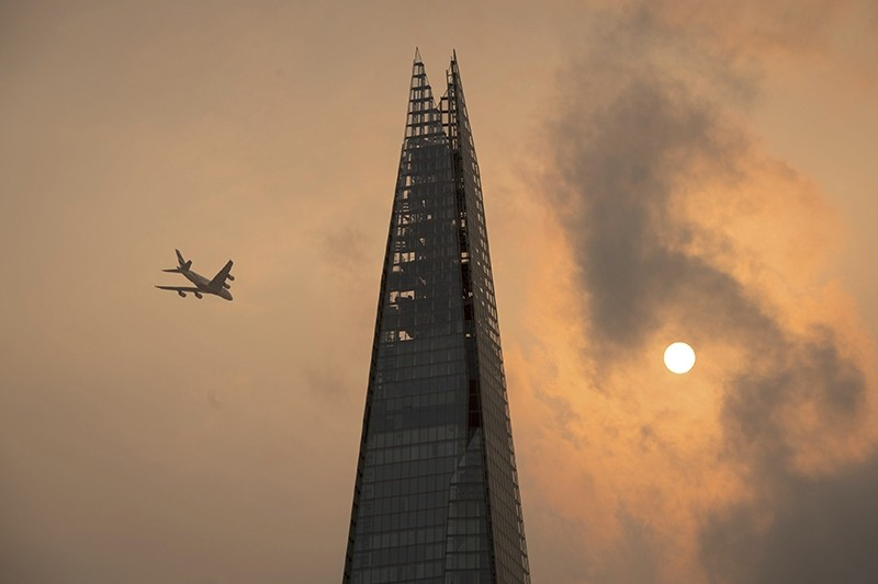 A plane flies past the Shard in central London, as the sky takes on an unusual orange colour caused by Hurricane Ophelia Monday Oct. 16, 2017.