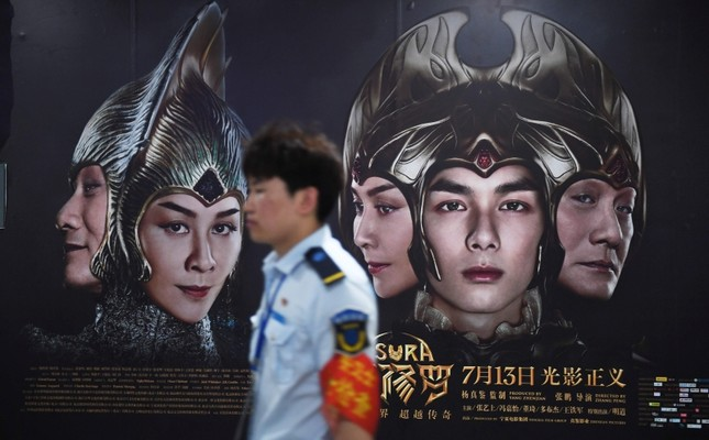 A railway worker walks past posters for the movie Asura at a subway station in Beijing, China, July 17, 2018. (AFP Photo)