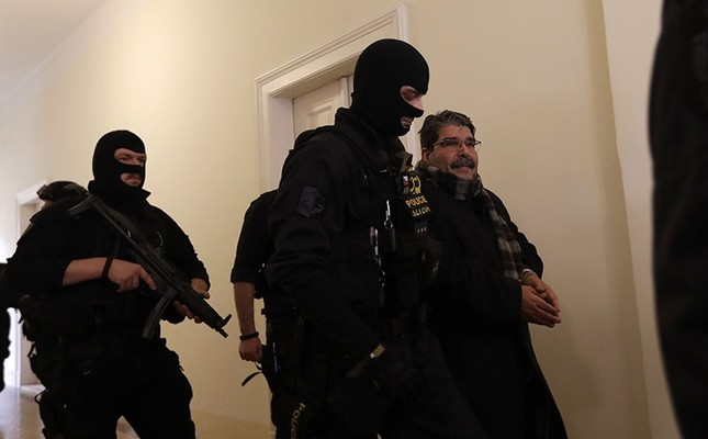Policemen escort Salih Muslim, former co-chair of the PKK-linked Democratic Union Party, or PYD, to a court room for a custody hearing in Prague, Czech Republic, Tuesday, Feb. 27, 2018. (AP Photo/Petr David Josek)