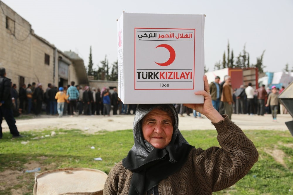 A woman carries an aid package of Turkish Red Crescent in Syria's Afrin.