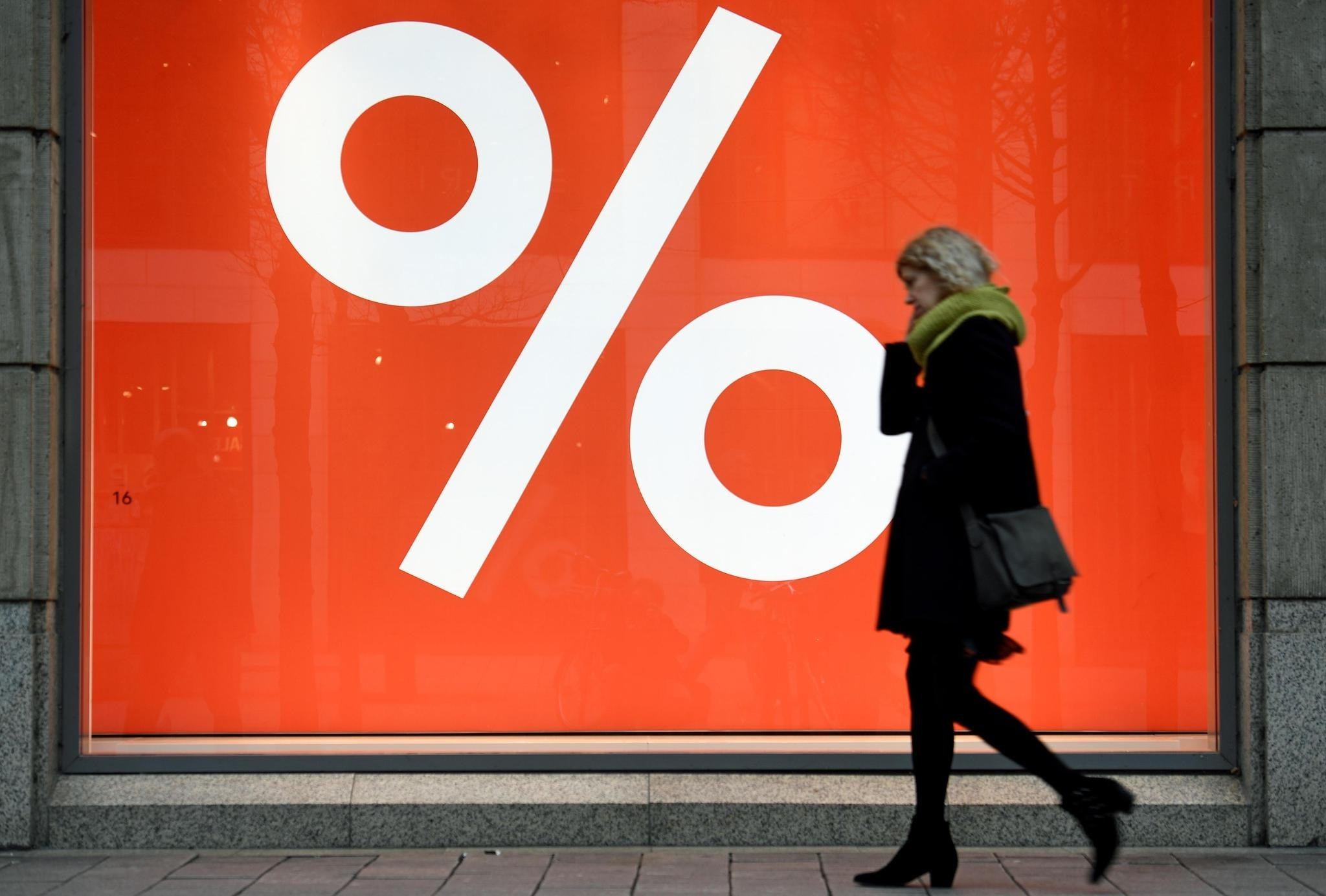 A woman passes a sale sign in a shop window in downtown Hamburg, Germany, January 25, 2018. (Reuters Photo)
