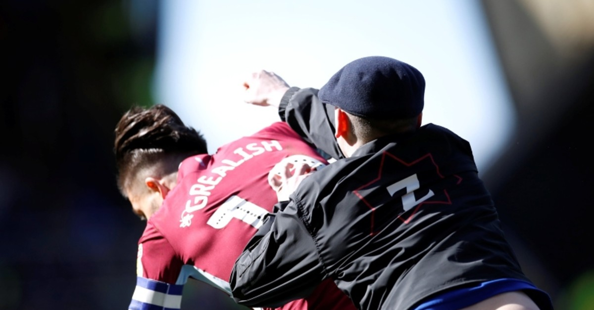 A fan invades the pitch and attacks Aston Villa's Jack Grealish during the match (Reuters Photo)