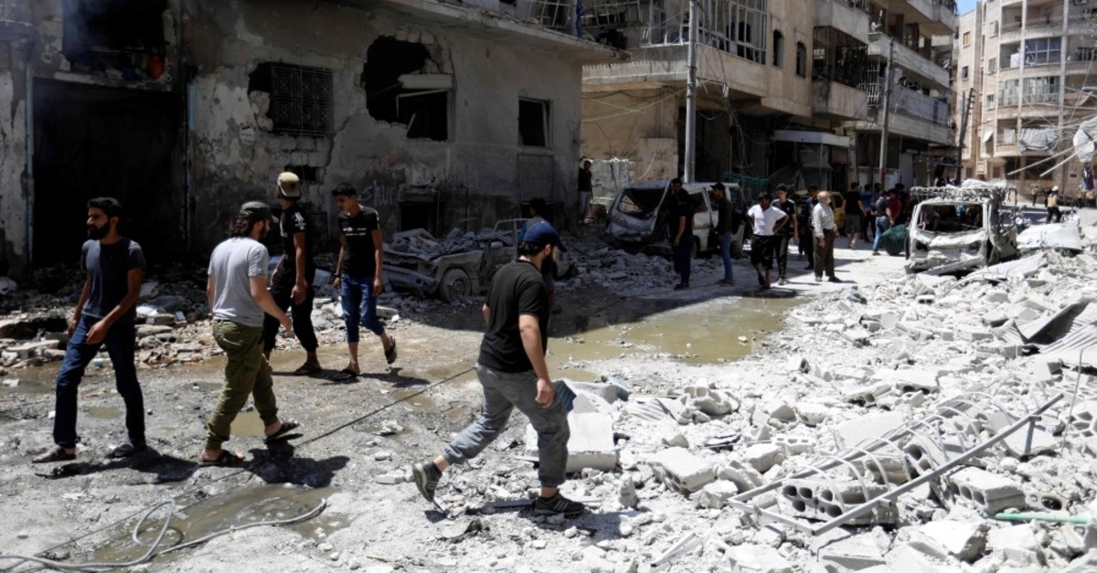 People gather at the site of a reported airstrike in Idlib, July 28, 2019.