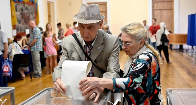 An elderly couple cast their ballot papers at a polling station during Ukraine's parliamentary election, in Kiev, on July 21, 2019. (AFP Photo)