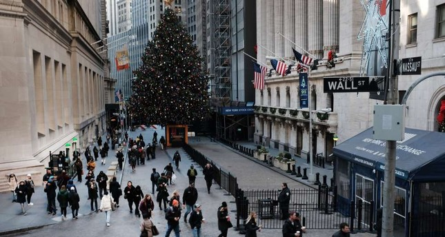 People walk by the New York Stock Exchange (NYSE) and the NYSE Christmas Tree in New York City, Dec. 17.