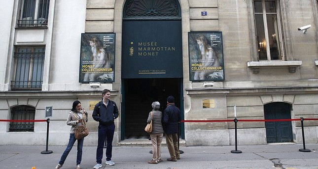 People wait outside the Marmottan museum in Paris, Tuesday, Oct.10, 2017. (AP Photo)