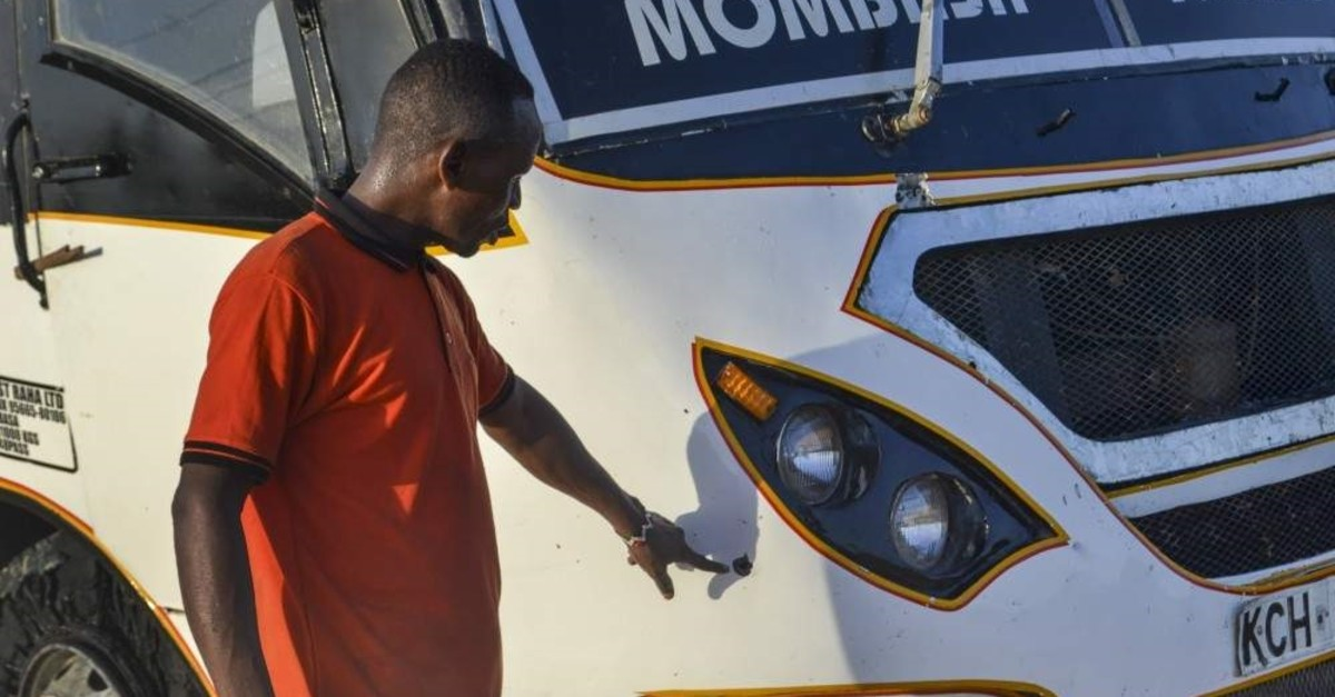 A man points at a bullet-hole on a bus which was ambushed by al-Shabab gunmen in the Nyongoro area of Lamu county, near the Indian Ocean coast of Kenya Thursday, Jan. 2, 2020. Kenyan police say four people have been killed in two ambushes. (AP Photo)