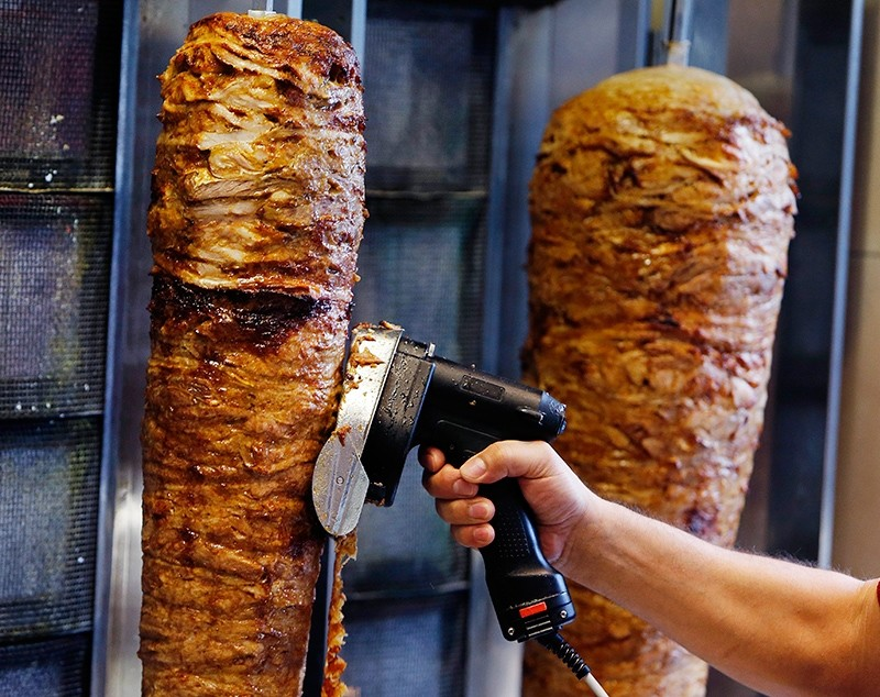 A man slices cuts of meat from a rotisserie Doner spit inside a Du00f6ner restaurant in Frankfurt, Germany, Nov. 30, 2017. (AP Photo)
