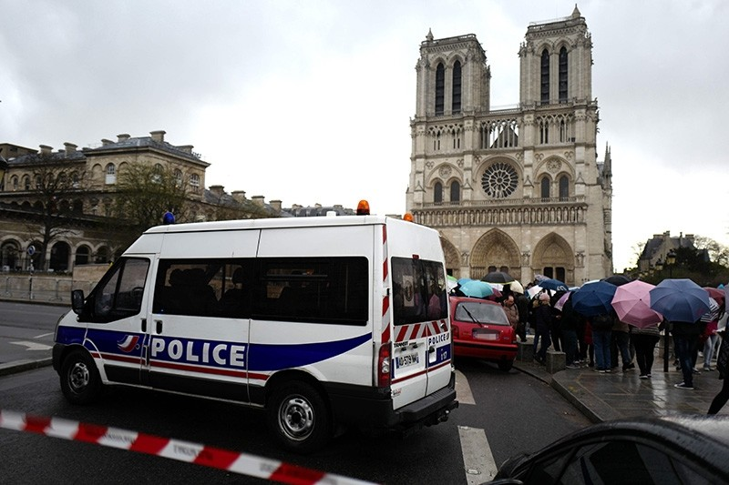 A police vehicle blocks the street as people queue to enter Notre-Dame de Paris Cathedral during the celebrations of Easter's Holy Thursday on March 29, 2018 in Paris. (AFP Photo)