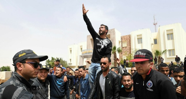 Tunisian protestors shout slogans during a visit by their prime minister in the town of Tataouine on April 27.