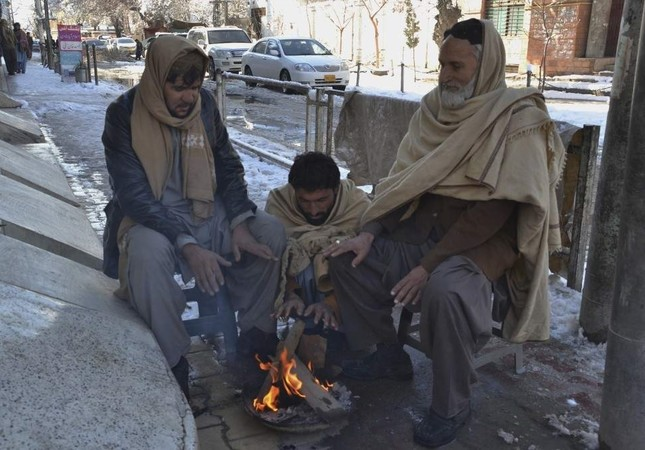 People sit around a fire after heavy snowfall in Quetta, the capital of Pakistan's southwestern Baluchistan province, Jan. 13, 2020. AP Photo
