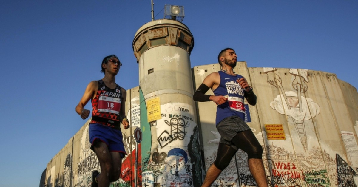 Runners pass by the Israeli separation barrier during the Palestine Marathon, in the West Bank city of Bethlehem, Friday, March 22, 2019. (AFP Photo)