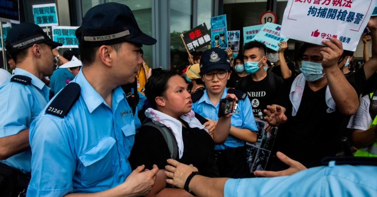 Police hold back an anti-extradition protester (C) during a rally in support of police outside the Legislative Council in Hong Kong on June 30, 2019 (AFP Photo)
