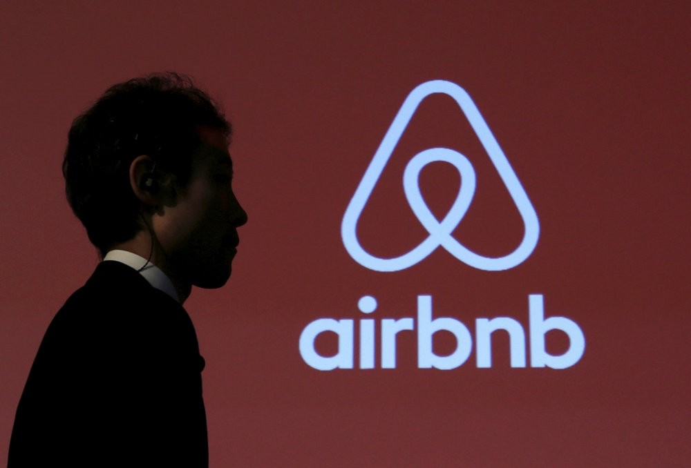 A man walks past a logo of Airbnb after a news conference in Tokyo.