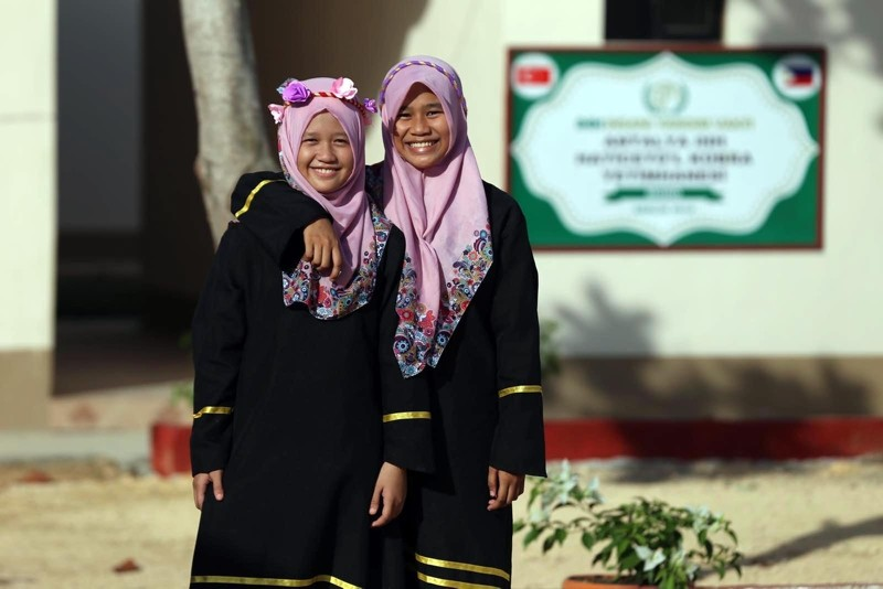 Two Muslim women living on the southern Philippine island of Mindanao stand next to a development project completed by Turkey's IHH aid agency in December 2018. (AA Photo)