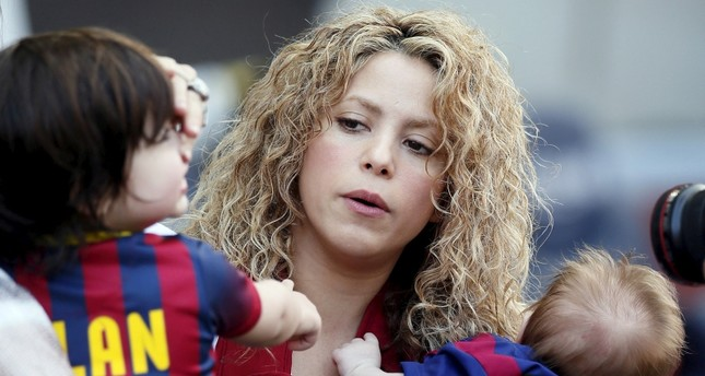 Singer Shakira (C) holds her sons Sasha (R) and Milan (L) before the Spanish first division soccer match between Barcelona and Valencia at Camp Nou stadium in Barcelona, April 18, 2015. (Reuters Photo)