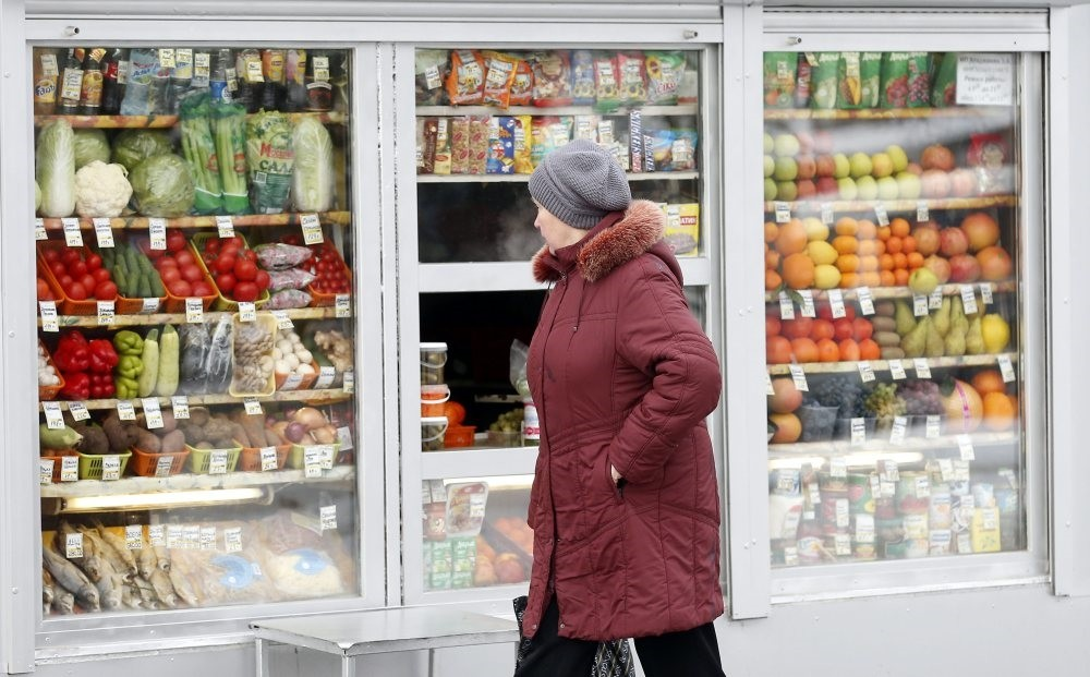 A Russian woman peers through the window to view fruits and vegetables at a street side market in Moscow.