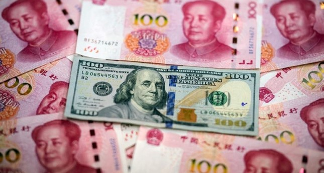 This photo illustration shows Chinese 100 yuan notes and a U.S. 100 dollar note in Beijing on Jan. 14, 2020. AFP Photo
