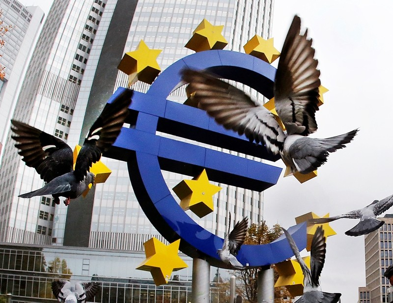 In this Thursday, Nov. 10, 2016 filer, Pigeons fly in front of the Euro sculpture at the old European Central Bank bulding in Frankfurt, Germany (AP File Photo)