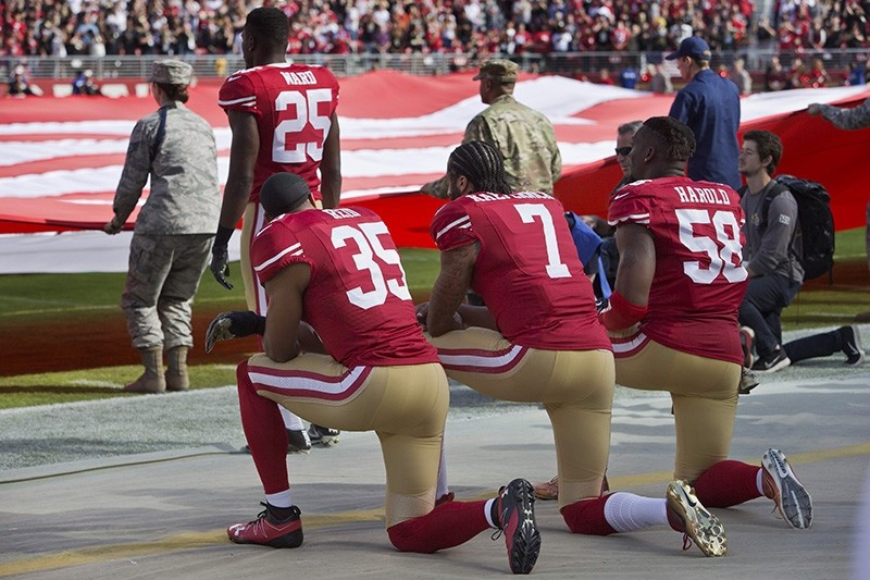 In this file photo taken Nov. 6, 2016 Quarterback Colin Kaepernick #7, safety Eric Reid #35, and linebacker Eli Harold #58 of the San Francisco 49ers kneel before a game against the New Orleans Saints in Santa Clara, California. (AFP Photo)