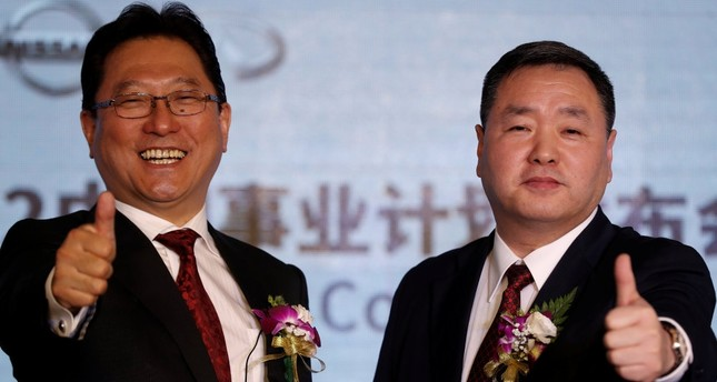 Jun Seki (L), the president of Dongfeng Motor Co., the Nissan and Dongfeng Group joint venture, and its Executive Vice President Lei Ping give the thumbs-up during a news conference in Beijing.