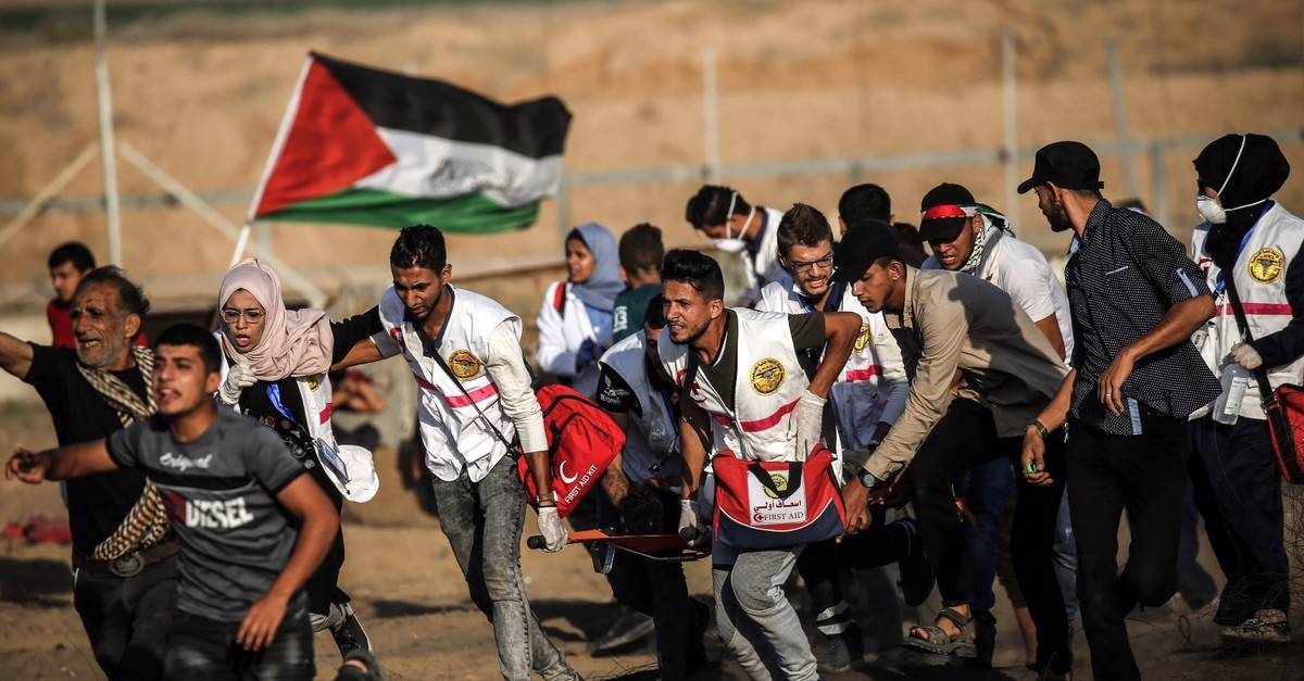 Palestinian paramedics carry away a protester injured by Israeli forces, the Gaza Strip, Sept. 27, 2019.