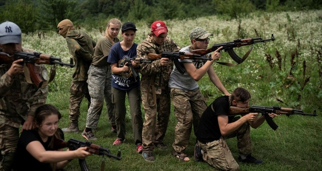 In this July 29, 2018 photo, young participants of the Temper of will summer camp, organized by the nationalist Svoboda party, practice tactical formations with AK-47 assault rifles in a village near Ternopil, Ukraine. (AP Photo)