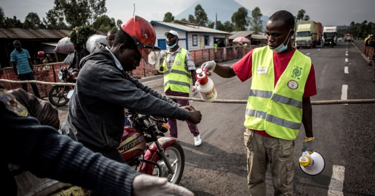 A motor taxi driver gets his hands washed at an Ebola screening station on the road between Butembo and Goma on July 16, 2019 in Goma. (AFP Photo)
