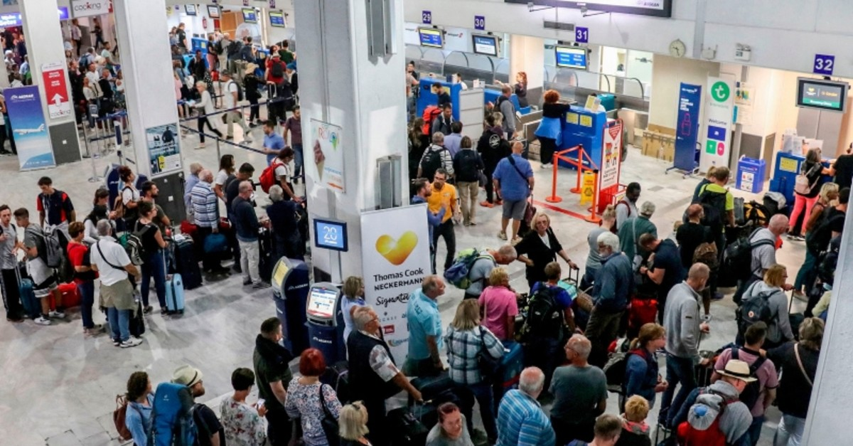 Tourists wait at a Thomas Cook company counter at Heraklion airport on the island of Crete on September 23, 2019. (AFP Photo)