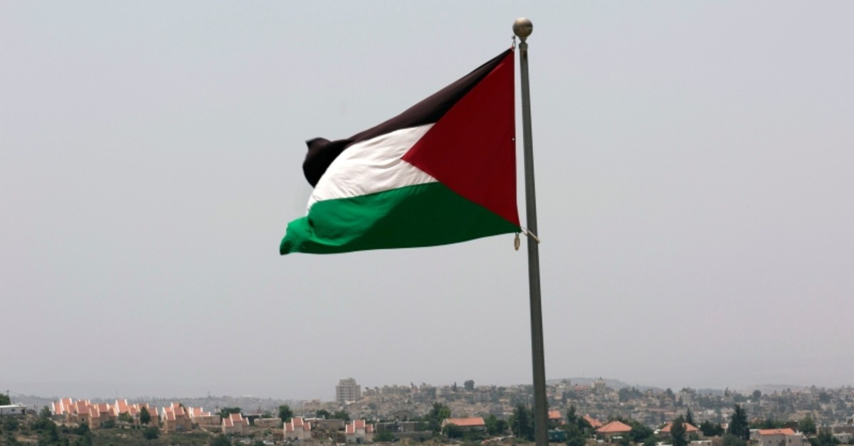This June 4, 2016 photo, shows the Israeli settlement of Ateret, background, as the Palestinian national flag flies from the highest point of the new West Bank Palestinian city of Rawabi, north of Ramallah. (AP Photo)