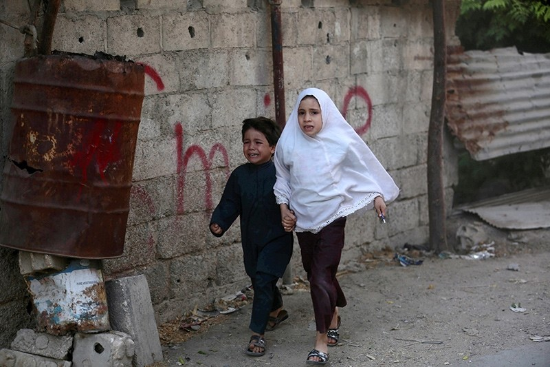 Syrian children run for cover following a reported airstrike on Kafr Batna, in the opposition-held Eastern Ghouta area, on the outskirts of the capital Damascus (AFP Photo)
