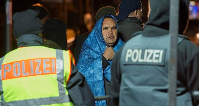 An Afghan refugee wrapped in a blue blanket to protect himself against the cold waits to cross into Germany. (File Photo)
