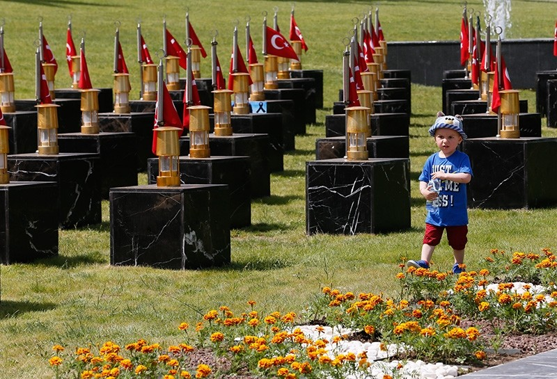 Three-year-old Hu00fcseyin Ferhat Avkau015f, named after his grandfather Hu00fcseyin and uncle Ferhat who were killed in the Soma mining disaster, walks among the graves in the miners' cemetary, May 13, 2017. (AA Photo)