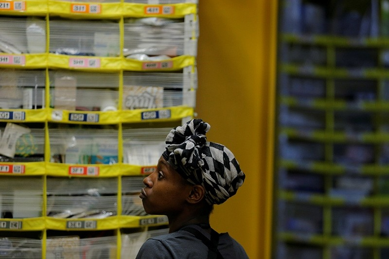 A worker sorts products into bins inside of a large Amazon fulfillment center in Robbinsville, New Jersey, U.S., Nov. 27, 2017. (Reuters Photo)