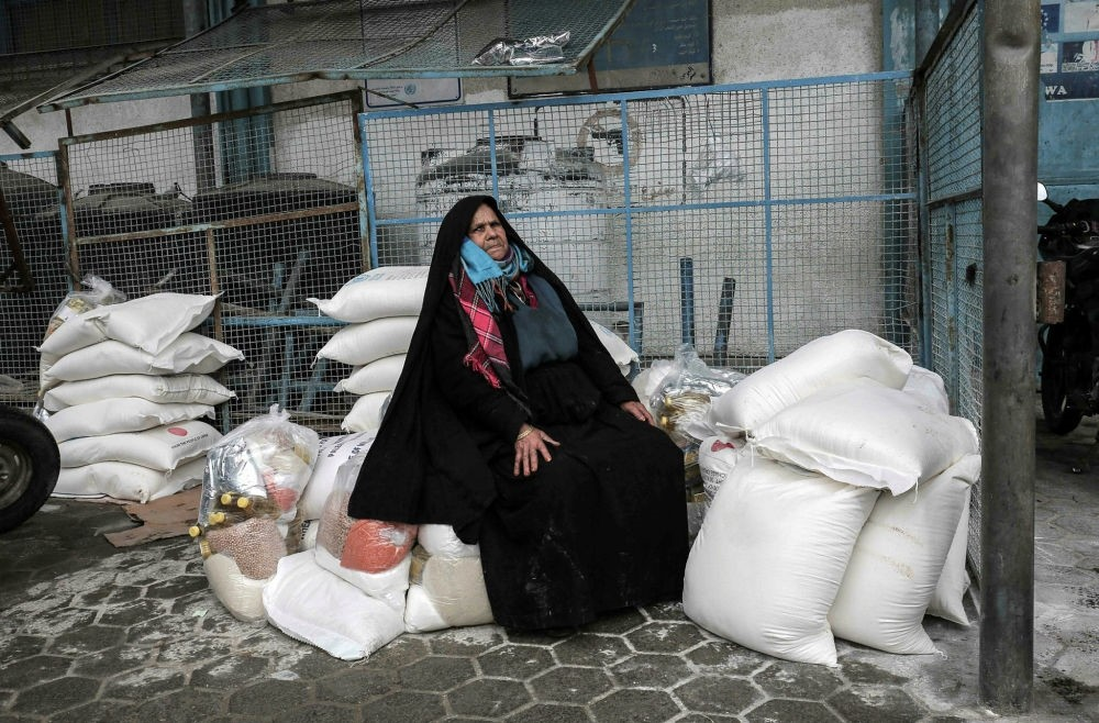 A Palestinian woman sits on a pile of food donations at a U.N. food distribution center in Khan Yunis, Gaza Strip, Jan. 28.