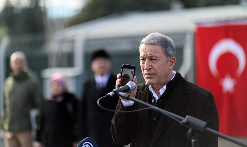 Defense Minister Hulusi Akar (R) holds a mobile phone as President Recep Tayyip Erdou011fan addresses soldiers via video call at the 2nd Army Tactical Operations Center in Hatay, Turkey on Jan. 20, 2019. (AA Photo)