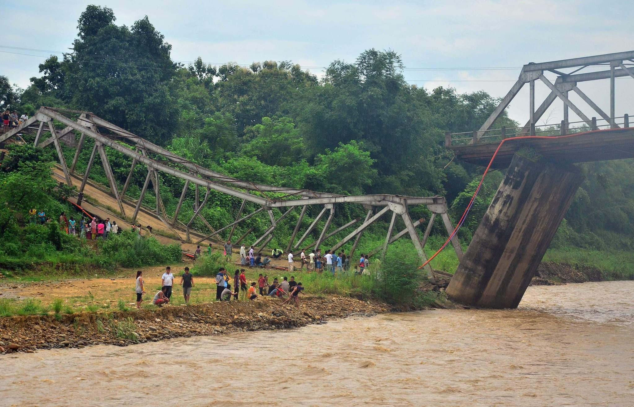 Indian bystanders look at a bridge that collapsed over the Chathe River in Dimapur, in India's northeastern state of Nagaland, on July 12, 2017. (AFP PHOTO)