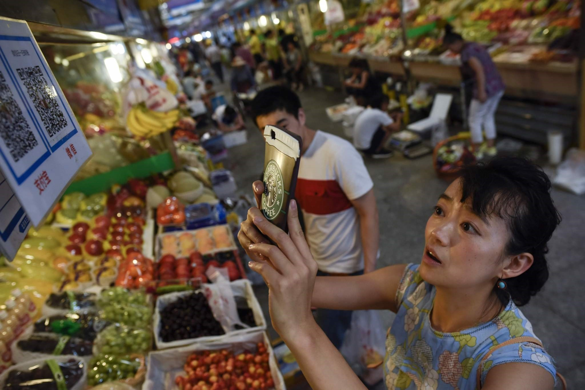 A woman makes purchases by scanning QR codes using her smartphone at a fruit stall in a market in Beijing.