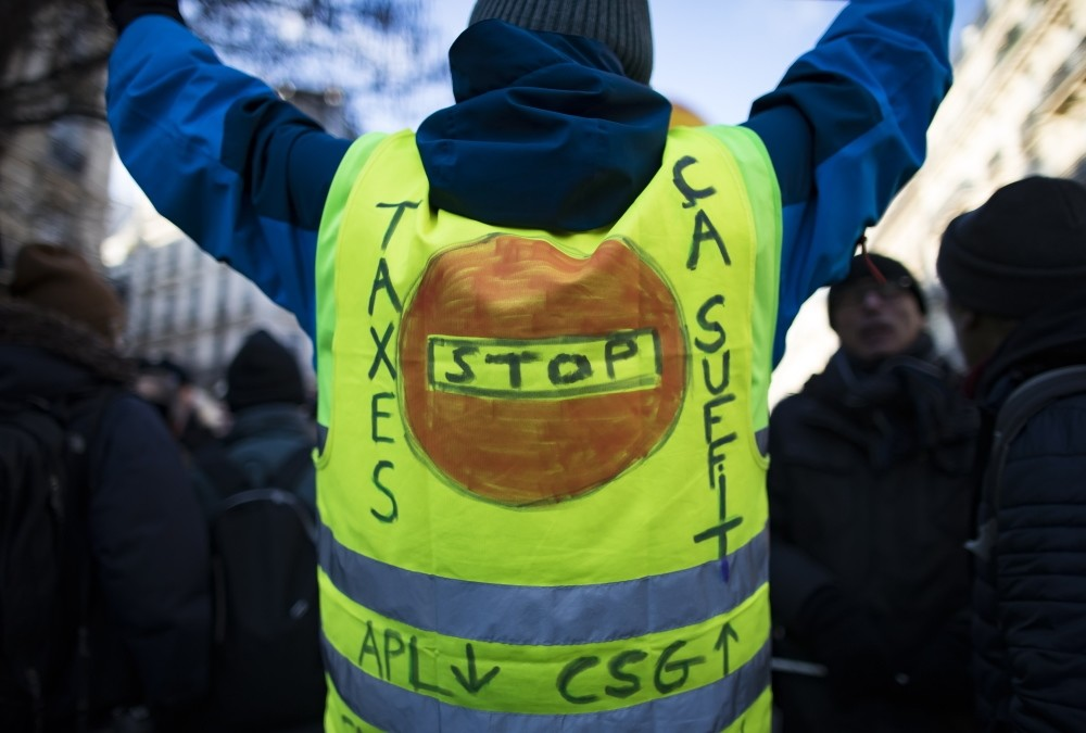 A yellow vest bears the message u2018Stop Taxesu2019 as high school students and union workers take part in a demonstration for pensions and social conditions, Paris, France, Friday.