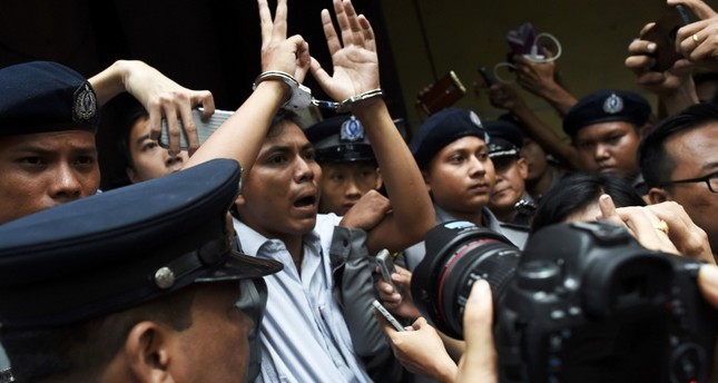 This file photo taken on September 03, 2018 shows Myanmar journalist Kyaw Soe Oo (C) is escorted by police after being sentenced by a court to jail in Yangon. (AFP Photo)