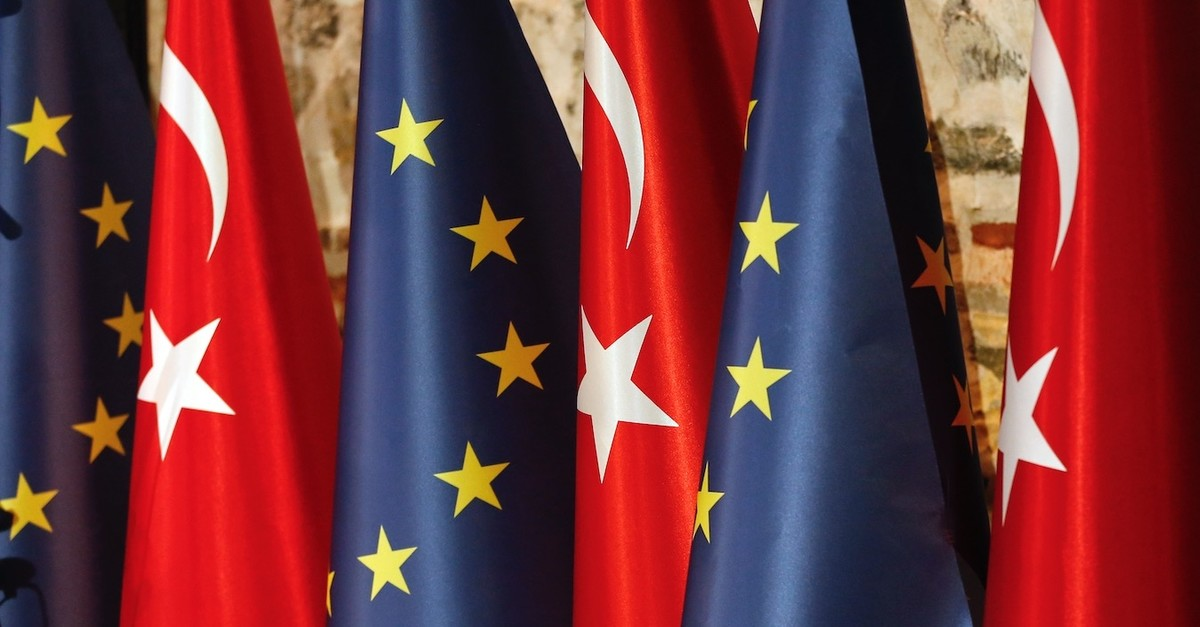 An official adjusts Turkish and European flags prior to the opening session of a high-level meeting between Turkey and the EU, Istanbul, Feb. 28, 2019.