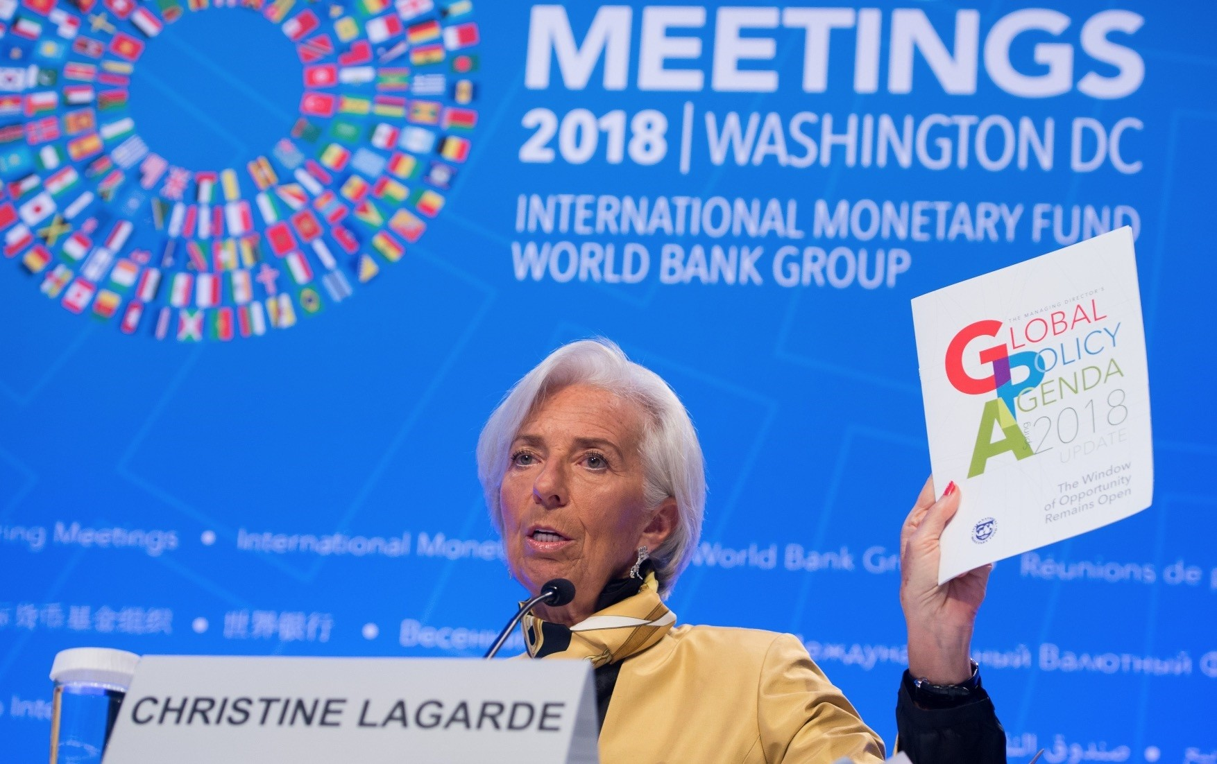 IMF Managing Director Christine Lagarde holds up a copy of the Global Policy Agenda as she holds a press conference during the 2018 Spring Meetings of the International Monetary Fund and World Bank Group at IMF Headquarters in Washington.