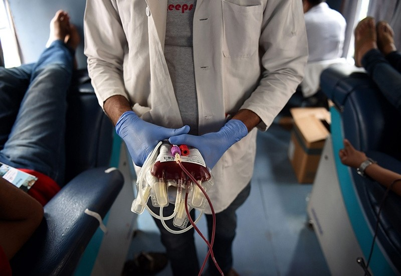 In this photograph taken on July 1, 2016, a worker separates bags of donated blood at a camp organised by the Rotary Blood Bank in New Delhi. (AFP Photo)